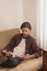 Man with his dog using mobile phone on sofa