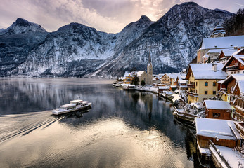 Hallstatt Christmas Village. Scenic postcard view of famous Hallstatt lakeside town in the Austrian Alps reflecting in Hallstattersee lake on a winter night with snow, Salzkammergut region, Austria.