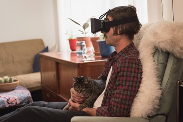 Man with his cat using virtual reality headset
