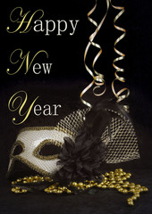 New Year's Eve themed image of gold and silver carnival mask decorated with black flower and feathers with curly ribbons on black background. Vintage filter and message added.