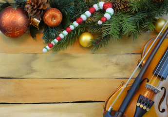 A miniature violin creates a border of artificial pine and holly with Christmas balls and and candy cane on a wooden background. Copy space.
