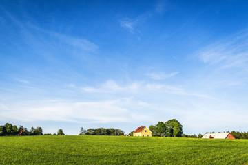 Yellow farmhouse on a rural green field