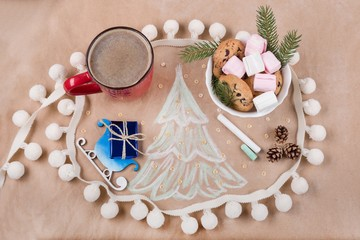 Christmas holiday background with gift box on the sled, coffee cup, cookies, cones, marshmallow, Christmas tree.