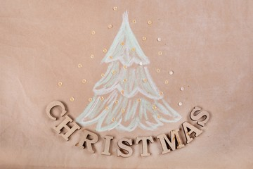 Christmas holiday background with Picture of a Christmas tree and text Christmas. Kraft paper background, View from above.