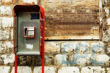 retro broken red phone booth box in front of rusty background and stone wall