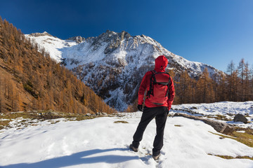 Man is backpacking in winter mountains. Piemonte, Italian Alps, Europe.