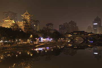 A Skyline Photo of Chendu from the River at Night, With City LIghts Burning Bright and a Bridge reflecting in the still water. Taken in Chengdu, China