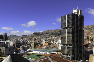 A View from above of the Sprawling cit of La Paz, Bolivia. A tall office block is in the foreground and clay roofs stretch as far as the horizon in the valley