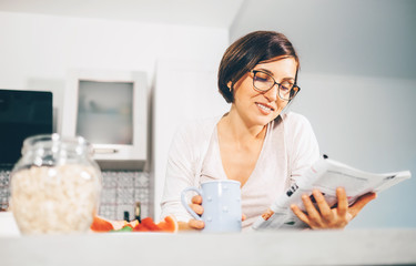 Woman reads a magazine and drinks morning tea on the kitchen
