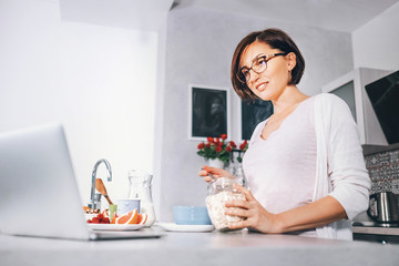 Woman prepare breakfast and watch a news in laptop