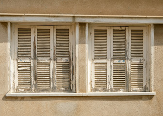 Old windows with closed worn wooden shutters.