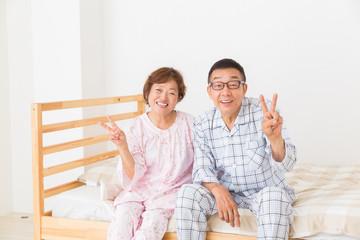 パジャマを着たシニア夫婦 ベッド