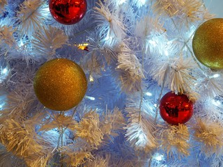 Many golden and red ornament balls on white Christmas. Can use for background or add text.