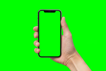Man's hand shows mobile smartphone with green screen in vertical position isolated on green background Wall mural