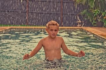 A boy is splashing water in a swimming pool.