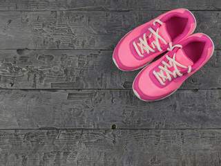 Beautiful pink women's running shoes dark vintage on the floor. The view from the top.