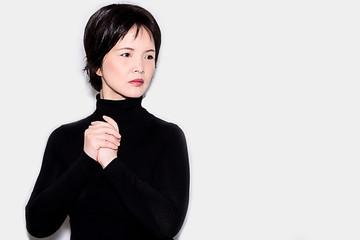 A portrait of an oriental woman wearing a black turtleneck sweater