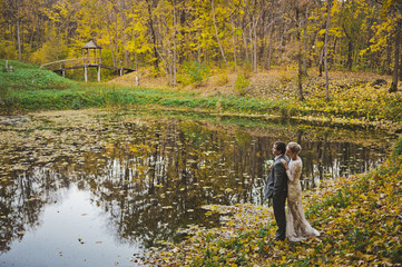 A dreamy portrait of the newlyweds on the shore of a forest lake in autu