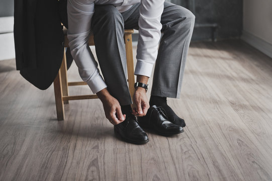 A man in a business suit ties the laces 336.