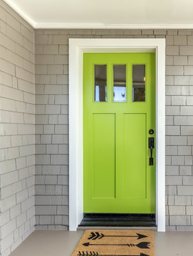 A front entrance of a home with a green entry door, front door & door mat