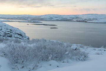 Trees covered with frost,the hills in the snow and the bay.