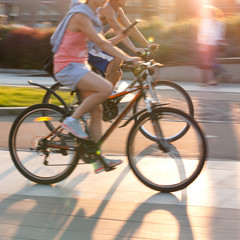 a boy and a girl ride bicycles down the street on a sunny summer day