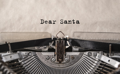 Dear Santa printed on an old vintage typewriter, close-up. Letter to Santa Claus with wishes for gifts, Christmas, New Year.