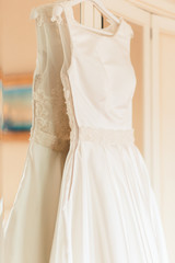 Wedding dress hanging on the wardrobe in the bedroom. The wedding collection. Classic expensive dress for a wedding or celebration in the room of an expensive hotel. Closeup. Vintage tonted photo.