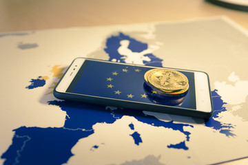 Financial concept with golden Bitcoin over smartphone, EU flag and map.