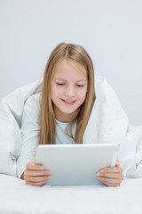 Teen girl using tablet pc on the bed under blanket