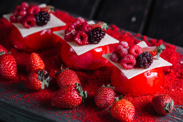 French berries mousse cake served on red sugar on wood background