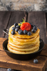 Pancakes with honey, bluberries and strawberry in a pan on a wooden cutting board on wooden background