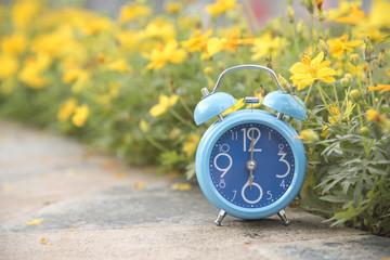 Blue clock in soft pastel blush background