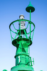 green lateral buoy against blue sky
