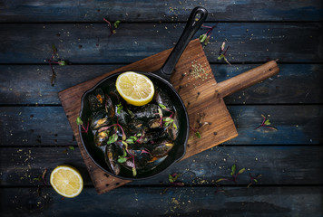 Delicious mussels. Serving on a hot frying pan with herbs spices and lemon on a colored wooden background. Top view