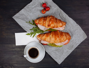 Tasty croissant lying near cup of coffee