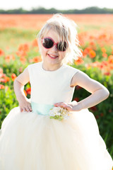 little girl model, childhood, happiness, fashion, summer concept - little girl blonde in a white outfit and sunglasses, stands amid fields of red poppy flowers, hands on her waist, smiling sweetly