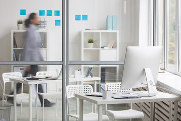 Business workplace by transparent wall and moving businessman behind it