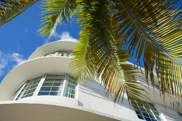 Classic curved 1930s Art Deco-era architecture and palm trees against blue sky on Ocean Drive in South Beach, Miami, Florida, USA
