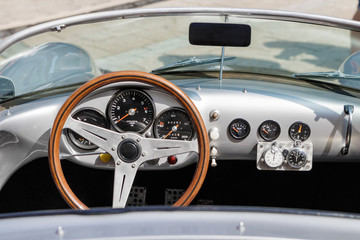 Close-up, detailed photo of the interior, dashboard, steering wheel and speedometer of a classic oldtimer luxury sports car.