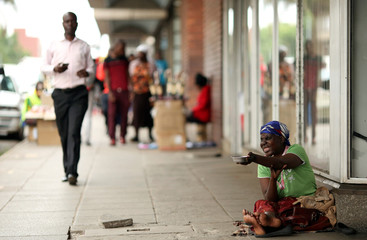 A women reacts as she begs for money in Harare, Zimbabwe