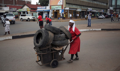 A women pushes a cart carrying used tyres for recycling in Harare, Zimbabwe