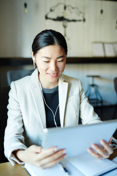 Asian businesswoman with earphones and tablet taking part in online conference or webinar