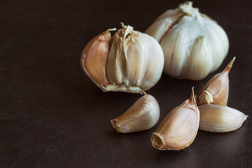 Fresh garlic put on black granite table in side view with copy space, isolated background. Food preparation concept for spices and herbs in still life idea...