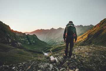 Man hiking at sunset mountains with heavy backpack Travel Lifestyle wanderlust adventure concept summer vacations outdoor alone into the wild Wall mural