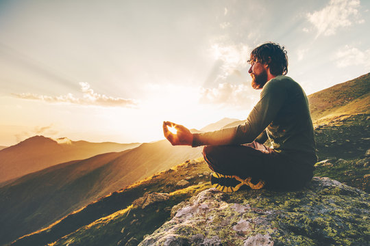 Man meditating yoga lotus pose at sunset mountains Travel Lifestyle relaxation emotional concept summer vacations outdoor harmony with nature calm scene