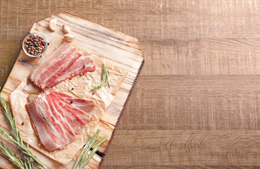 Rashers of bacon on wooden board