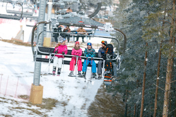 Family with chair lift going on ski terrain