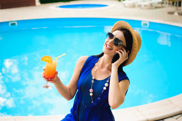 Beautiful young woman with phone near swimming pool