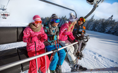 Family going on ski terrain with ski lift